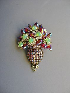 It measures about 1 and 1/2 x 2. Aurora light green and red crystal stones on Gold tone metal. Real crystal. Beautiful brooch! Leverback type closure with secure latch. Inspired by vintage fashioned. Pin is signed SNK. This brooch is in excellent condition with only some slight tarnish.