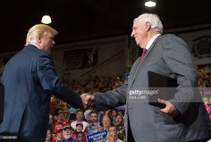US President Donald Trump (L) shakes hands with West Virginia Governor Jim Justice, who announced during the rally he would switch parties from Democrat to Republican, during a Make America Great Again Rally at Big Sandy Superstore Arena in Huntington, West Virginia, August 3, 2017. /
