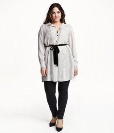 Lang tunika i blød, vævet kvalitet med trykt mønster. Den har knaplukning foran og lange ærmer, slids i siderne og lidt længere bagstykke.