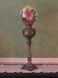This is an absolutely beautiful Turn-of-the Century parlor lamp. Manufactured by Bradley and Hubbard in the late 1800 it was originally a gas lamp, it was later converted to electric as many of these beautiful showpieces were when more and more homes were updated with electricity. The wiring on this lamp still works but it is old and should be re-wired for safety. The cast metal base has a very detailed pattern of flowers and scrolls and the round glass shade is handpainted. Very tall, it…