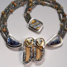 JILL TOWER It has taken me 4 months to complete, but here is my double barn owl necklace. Labor of love - feels so good to be done! The faces and clasp are cloisonné enamel on silver. The body of the owls is fossil mammoth tooth. My dad slabbed that piece for me, and also cabbed the 2 pietersites on the necklace. The beads are labradorite and agate.