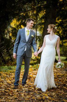 A wedding couple strolling through a park
