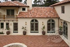 Exterior of a SPANISH STYLE LUXURY HOME with stucco walls a red tile roof and MEXICAN TILE PATIO (1886-5452 / EAG1193 © Stock Connection)