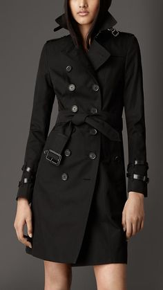 Long Leather Detail Gabardine Trench Coat by: Burberry @Burberry (US) The refined cotton gabardine trench coat features leather at the throat latch and double cuff straps. Invented by Thomas Burberry in 1879, cotton gabardine is a refined, tightly woven and breathable fabric that protects against wind and rain. Heritage details include epaulettes, gun flap and rain shield.