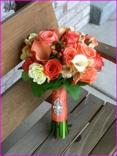 Gorgeous Wedding Bouquet Showcasing: Coral Roses, Coral Calla Lilies, Pink Alstromeria, Red Hypericum Berries, White Calla Lilies, White Lisianthus & Green Foliage