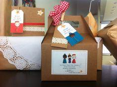 Caja de cartón kraft Reyes Magos Tamaño: 17 x 14.1 x 9.5 cm, decorada con:  Pegatina frontal de Reyes Magos, Etiqueta Kraft con puntilla, Etiqueta de Rey Mago (a elegir entre los 6 modelos que mostramos). Lazo cuadros rojos, Pinza de madera