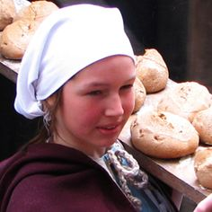 Photograph of a girl in medieval clothing carrying a long wooden tray of bread