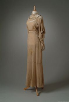 Gray-beige silk velvet evening gown accented on the small of the back with pleated, fan-shaped velvet. Details include a rhinestone clasp on the back and trim of silver braid. The sleeves are slit and weighted, which was popular in 1933.