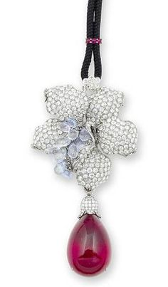 A rubellite, sapphire, ruby and diamond pendant/brooch. photo Bonhams Designed as an orchid, the petals pavé-set with rose-cut diamonds, the briolette-cut sapphires cascading off the centre, suspending a rubellite cabochon connected to a brilliant-cut diamond foliate cap, accompanied by a black cord necklace, with a rose and brilliant-cut diamond bail in floral motif design, by a row of ruby cabochons, mounted in 18k white gold,