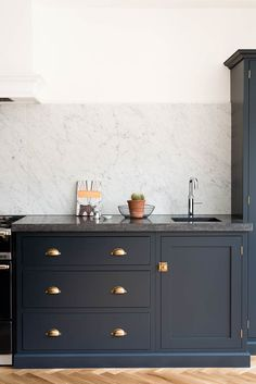 Belgian Blue Fossil worktops and a huge Carrara marble splashback make this Shaker kitchen
