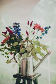 Watering can floral arrangement // Photo by Ahava Studios, see more: http://theeverylastdetail.com/colorful-handmade-new-york-wedding/