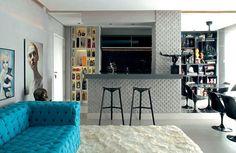 Sala de estar, jantar e cozinha americana integrados neste apartamento de um jovem médico, onde o cinza predomina para dar destaque aos pequenos objetos frutos de coleções do proprietário