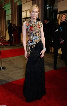 Colourful: The 46-year-old looked youthful in her directional glitzy Alexander McQueen gown, which hugged her willowy figure perfectly before falling into an ostentatious black feathered skirt