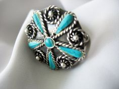 Mexican Turquoise five petal flower ring set in Sterling Silver, with lots of twisted wire detailing and darkened patina.  Ring sits about 1/4 inch