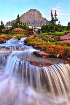 Amazing photo of waterfall, flowers, with a mountain backdrop.