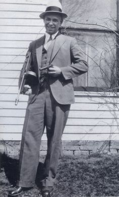 """On April 5, 1934, a month after his """"great escape"""" Johnnie Dillinger turned up at his father's farm for a family reunion under the very noses of the FBI. (Two agents were watching the house.) Here he poses with a Thompson sub-machine gun and the wooden gun he had used to escape the jail in Crown Point, Indiana on March 3rd, 1934."""