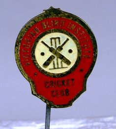 Badge for the Victorian Blind Institute Cricket Club, circa 1920s-1960s. Blind cricket was invented in Melbourne in 1922. In 1928 a cricket ground and clubhouse was developed at Kooyong, Melbourne.  Metal stick-pin badge used by the Victorian Blind Institute Cricket Club. with a central image of two crossed cricket bats in front of a set of wickets and two dots, perhaps representing cricket balls.  Victorian Blind Institute Cricket Club, Prahran, Victoria, Australia, circa 1920s-1960s