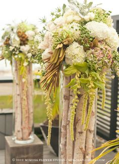 Incredible birch filled vases with a white hydrangea arrangement.