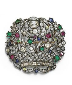 GEM-SET AND DIAMOND BROOCH Of giardinetto design set with mixed-cut rubies, emeralds, sapphires, demantoid garnets and highlighted with variously cut diamonds.