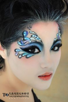 Gorgeous purple and blue fantasy eye make-up accented with opalescent jewels.