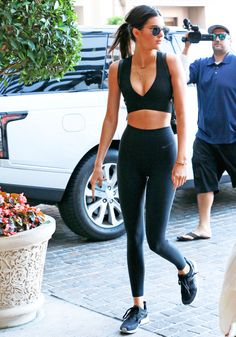 She hits the streets in L.A. donning a sporty crop top, high-waisted leggins, and trainers.   - MarieClaire.com