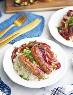 Instant Pot Bangers and Mash with Onion Gravy on a white plate; forks and knifes in the background.