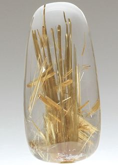 RUTILATED QUARTZ (polished) ~ An elongate cabochon of Quartz included by Rutile. Golden needles of Rutile to 4.6cm long form reed-like inclusions in gemmy water clear Quartz.