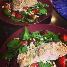 Cashew crusted salmon on a bed of spinach, green leaves and strawberries... recipe through Tone it Up nutritional plan!