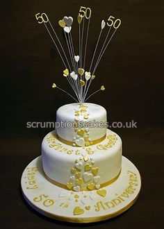 www.scrumptiouscakes.co.uk (720) - 2 tier golden wedding anniversary cake with gold and white hearts, names and message.