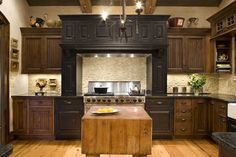 Black cabinets with a distressed finish make the range and vent hood the focal point of this kitchen.