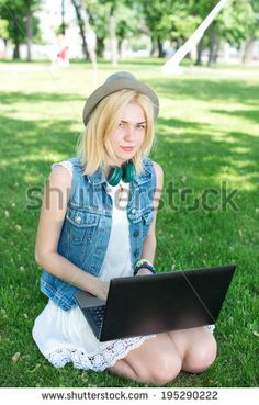 Mixed race college student sitting on the grass working on laptop at campus - Shutterstock Premier