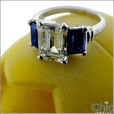 An interesting three-stone ring with high polished solid shank and AAA high quality emerald cut cubic zirconia center stone with emerald cut sapphire cubic zirconia on each side Shape EmeraldCarat Weight center sides TCW 3 Solid Gold, White Gold, Sapphire Color, Cubic Zirconia Rings, Three Stone Rings, 2 Carat, Eternity Bands, Emerald Cut, Emeralds