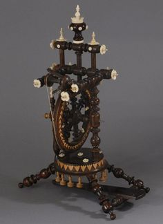 "Austrian flax wheel. The turned details are plentiful, and include many intricately carved finials in bone. Also, note the applied ornamentation in lighter woods – especially the row of bell-shaped drops that finish the bottom.   Measures: 15"" tall"