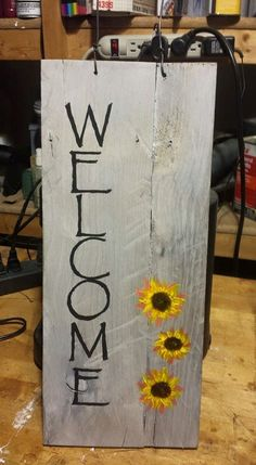 A simple sign made with pallet boards, vinegar and steel wool aging, hand lettering and some painted flowers