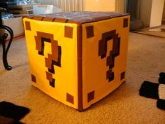 Super Mario World Question Mark Block Ottoman.   The Super Mario World Question Mark Block Ottoman would look great in any geeks apartment, it measures 15 x 15 x 15 inches and is made from memory foam and covered in vinyl.
