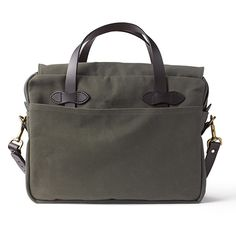 """Filson's ruggedly durable, water-repellent briefcase has a large interior compartment with dividers for laptop and accessory organization. An adjustable Bridle Leather shoulder strap and handles round out this handsome, reliable briefcase. Features Zipper and storm flap closure 2 stow pockets, 3 interior dividers Abrasion- and water-resistant fabric Removable, adjustable 46""""-long Bridle Leather shoulder strap with pad Large inner compartment with dividers Meets standard airline carry-on…"""