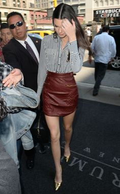 Kendall Jenner in a striped blouse and leather mini skirt