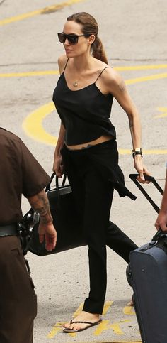 Dark Storm WHO: Angelina Jolie WHAT: Saint Laurent top, pants, and bag WHERE: Boarding a plane in Hawaii WHEN: July 10, 2013