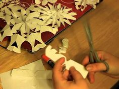 3-D snowflake video tutorial. the secret is tying a string in the center of the fan-folded paper.