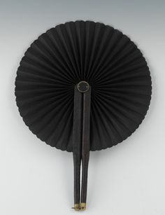 """An American Mourning Fan, ca. Civil War Era   6""""L  The two sticks are clad in leather with brass tip at the ends, hinged at the top and opening the silk fan in a circular fashion, all in black, the ring at the tip would clip to the other stick to hold it open.  Apprx. 9-1/4""""L."""
