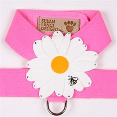 This pink dog walking harness is blooming with beauty! The unique floral dog harness designed by Susan Lanci features a large daisy flower with dimensional petals each accented with a sparkling Swarovski crystal. An embroidered bumble bee buzz