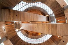 Architecture studio OMA has revealed images of the first completed part of its renovation of Berlin department store KaDeWe, a retail and event space connected by wood-clad escalators.