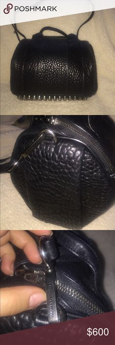 "Alexander Wang ""Rockie"" handbag in pebbled black Rockie sling with large main compartment and generous zipper opening. Exterior has black nickel studded bottom and hidden pocket on exterior side gusset. Adjustable shoulder strap with signature rhodium dog clip and two top handles. Polyester lined interior has zip pocket with Alexander wang logo patch and phone pocket. 100% lambskin. Item is slightly used, still has tags and will come with duster bag. Alexander Wang Bags Shoulder Bags"