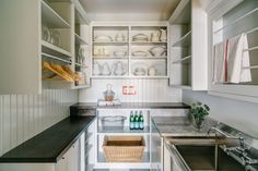 U shaped pantry boasts open display cabinets over white lower cabinets paired with a mix of soapstone countertops and white quartzite countertops and beadboard trim backsplash.