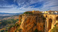 Ronda in the Province of Málaga, Spain Ancient civilizations used this mountain perch in the south of the Iberian Peninsula as a strategic location for fortified settlements, with Romans, Moors, and Visigoths each contributing to the modern-day Spanish city we now call Ronda. Puente Nuevo is the bridge we see on the right side of this picture. It's one of three bridges that straddle El Tajo canyon, the gap that separates Ronda's two halves. At the base of El Tajo runs the Guadalevín River…