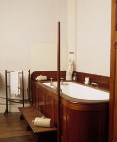 The bathroom at Dunster Castle showing the mahogany panelling enclosing the bath, access steps, stone hot water bottles, clothes horse and small porcelain figure on the bath surround  | National Trust Images