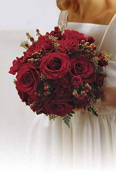 A Christmas wedding bouquet consist of red roses, delicate spray roses, ranunculus, hypericum berries & eucalyptus foliage.