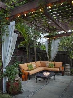Pergola, plants, string lights, curtains, orange couch and pillar candles...