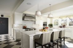 Perfect white kitchen, with checker marble floors, comfy island seating, subway tiles, and open view.