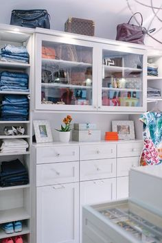 Jeans and shoes are stacked in cubbies flanking a built in dresser fitted with polished nickel knobs and topped with white framed photographs, small orange stacked boxes, and gray stacked decorative boxes located beneath glass front purse cabinets illuminated by custom lighting.